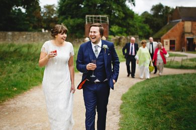 The bride and groom stood next to each other walking and laughing at Calke Abbey