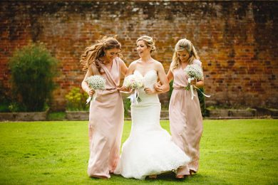 the bride and bridesmaids walking and laughing together