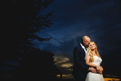 the bride and groom stood in a dark moody sky on their wedding day