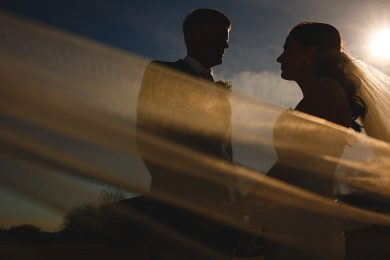 the bride and groom at Swancar farm stood in the sun with a veil blowing in the wind