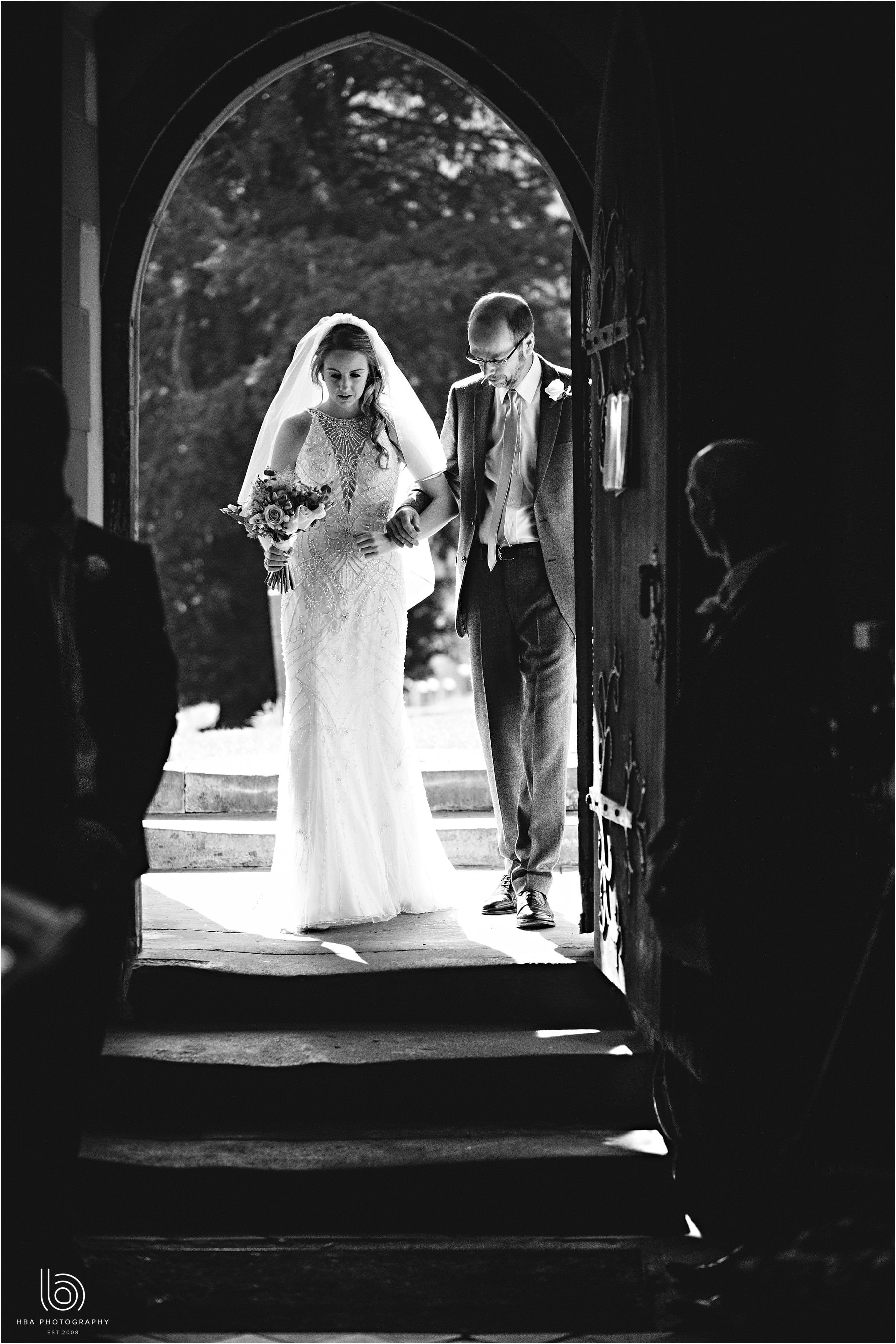 the bride and her dad walking into the church