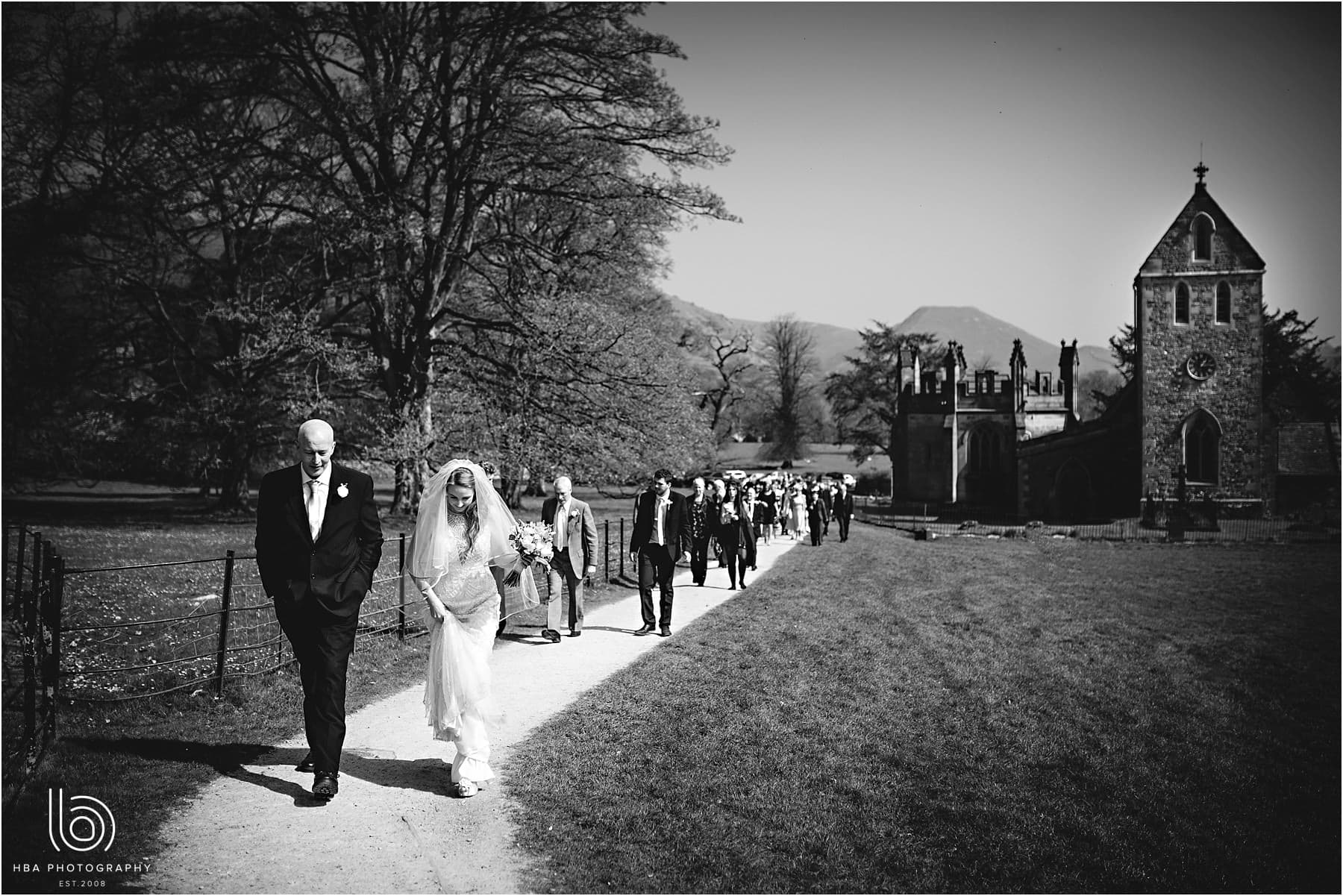 the bride and groom walking to Ilam Hall