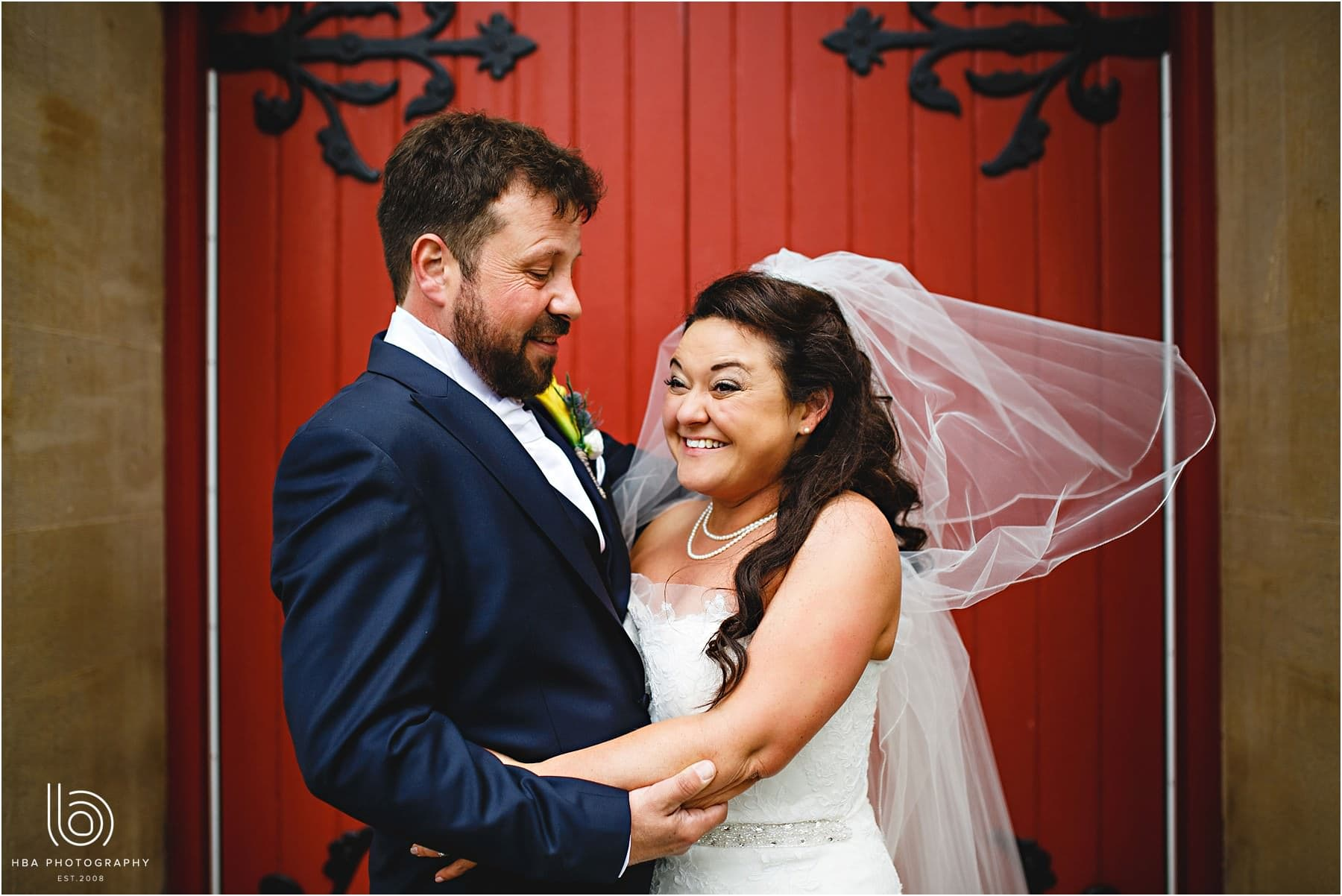 the bride and groom in front of a red door