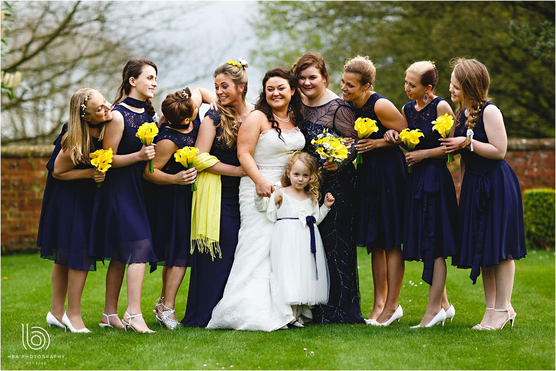 the bride and her bridesmaids in yellow and blue