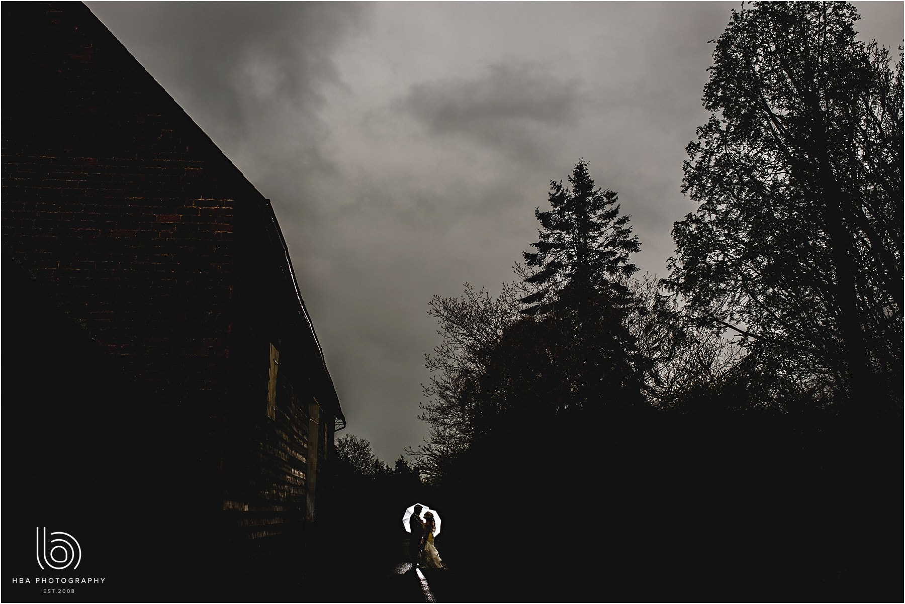 the bride and groom in silhouette in the rain