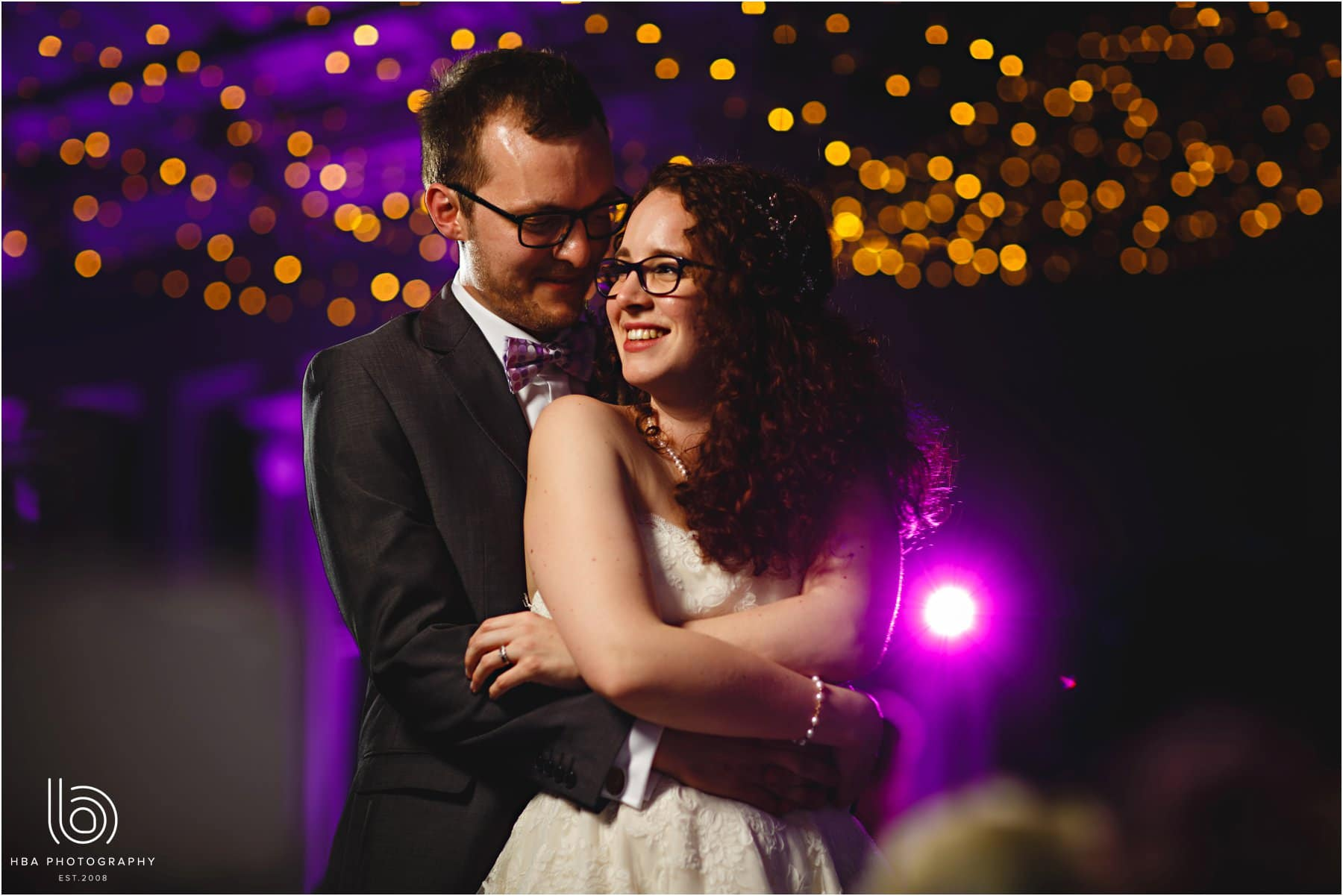 the bride and groom with fairy light back drop