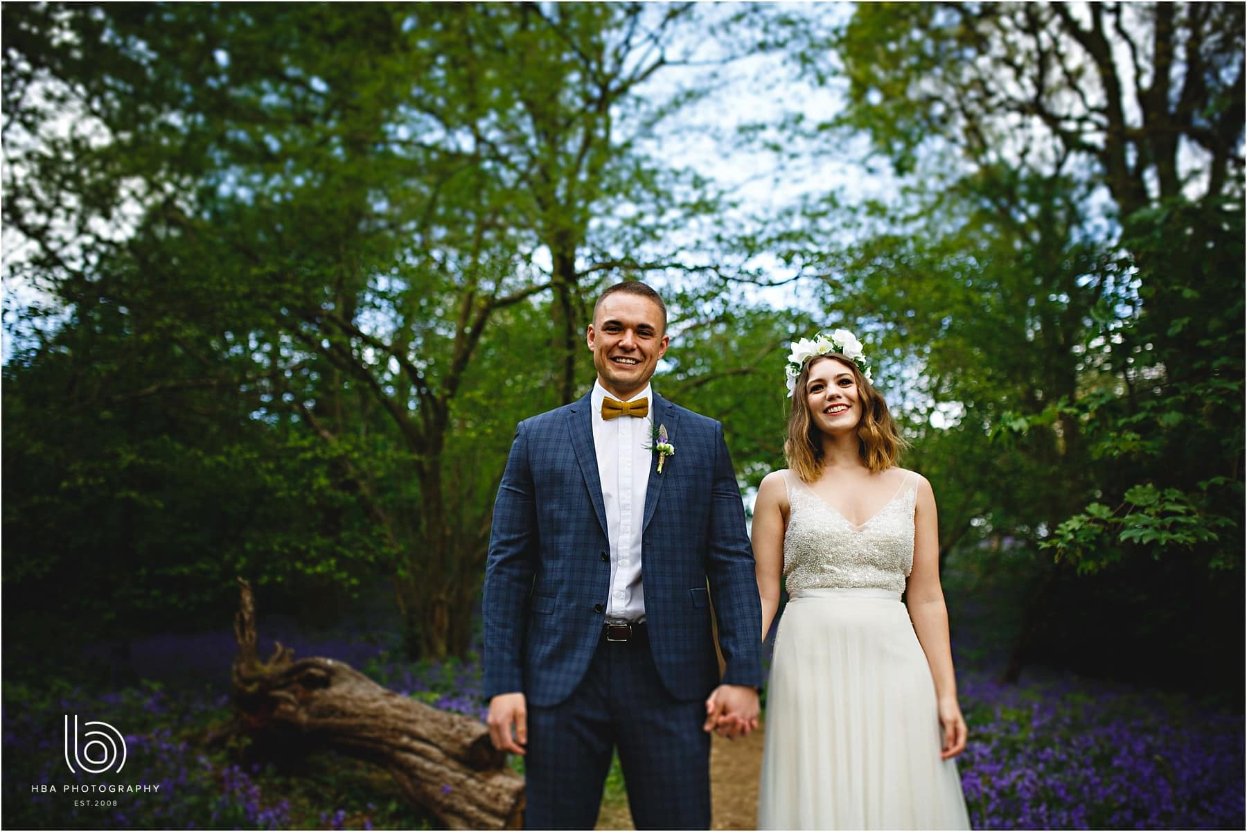 the bride and groom in the bluebell woods