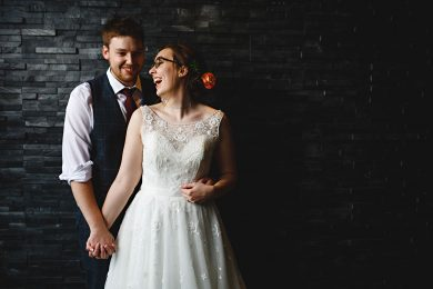 the bride and groom stood against a brick wall at The Peak Edge Hotel in Chesterfield, Derbyshire