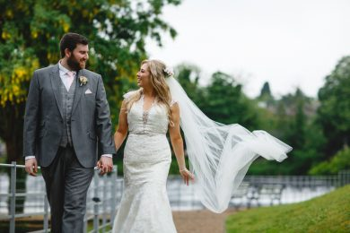 Te bride and groom walking away by the river at the west mill in Derbyshire