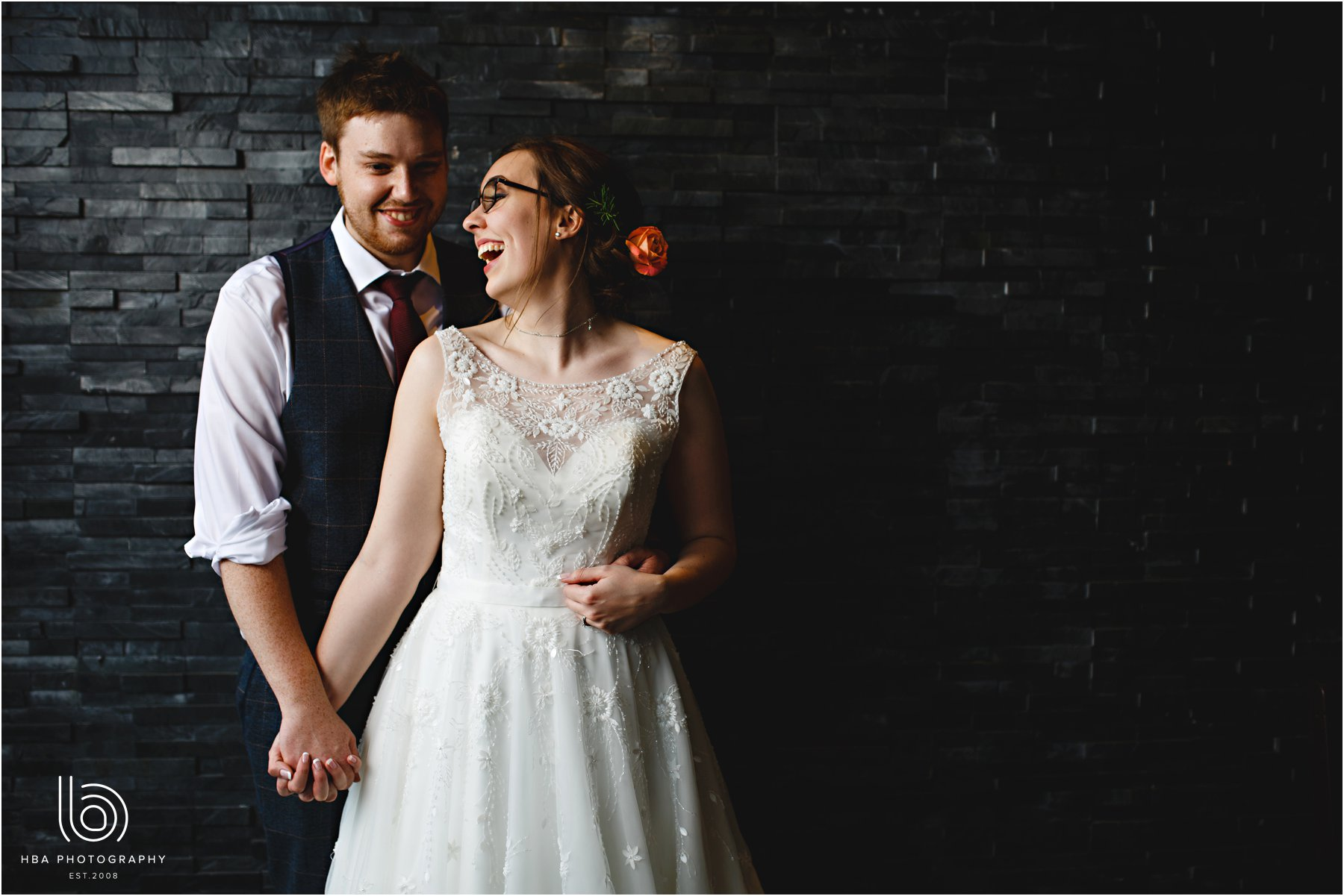 the bride & groom by a slate wall