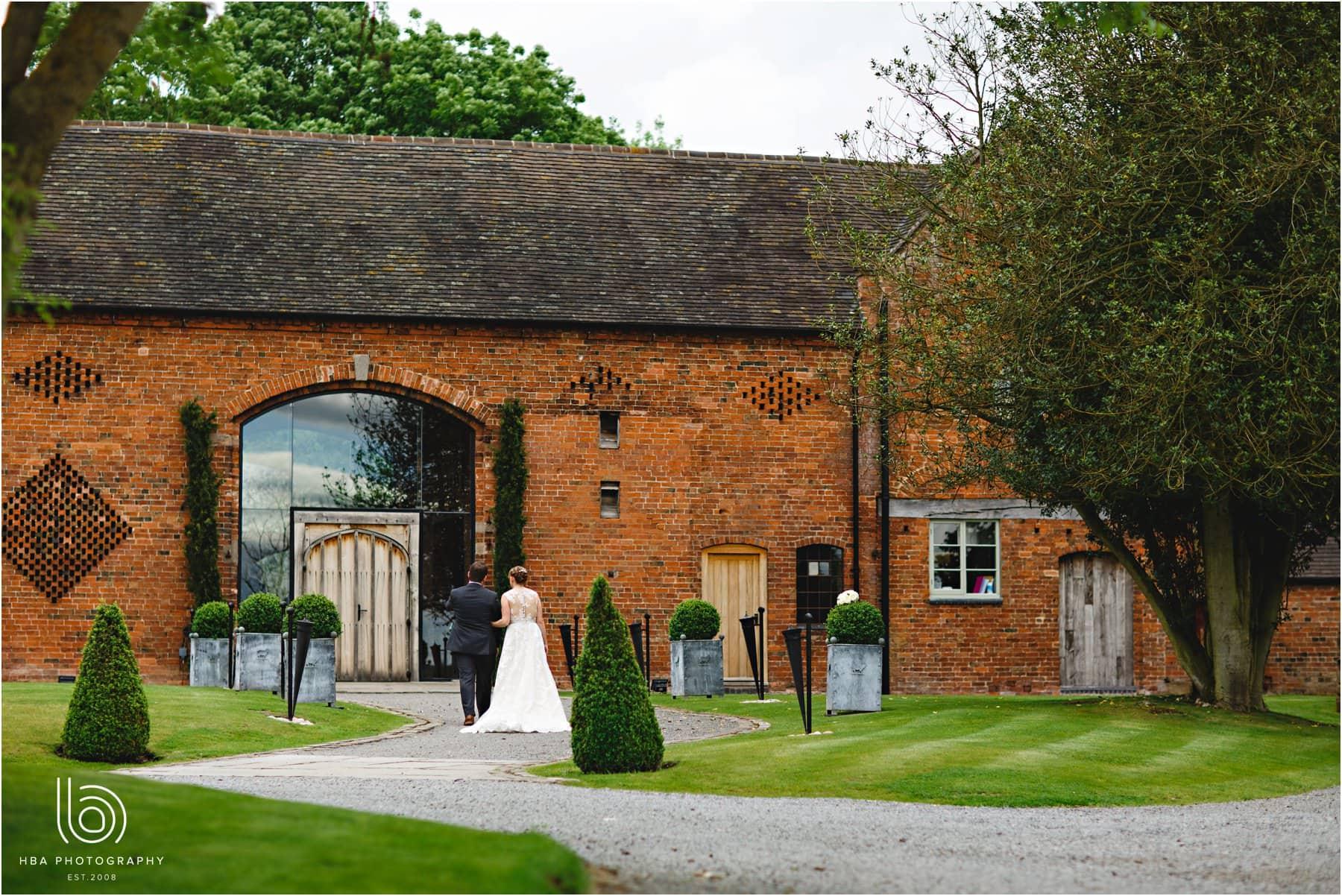 the bride & groom walking up to shustoke