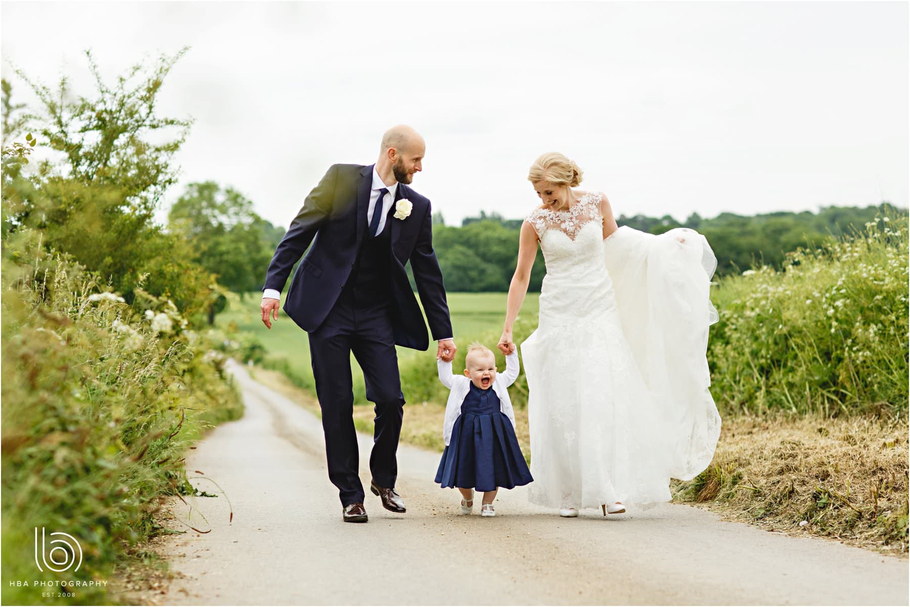 the bride & groom walking with their daughter
