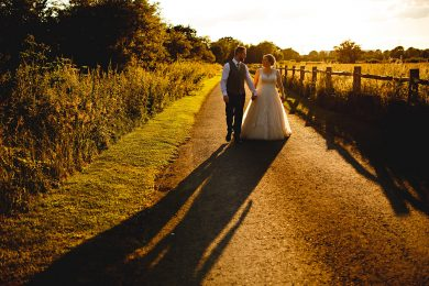the bride and groom walking towards the camera at shustoke farm barns in beautiful golden sunlight