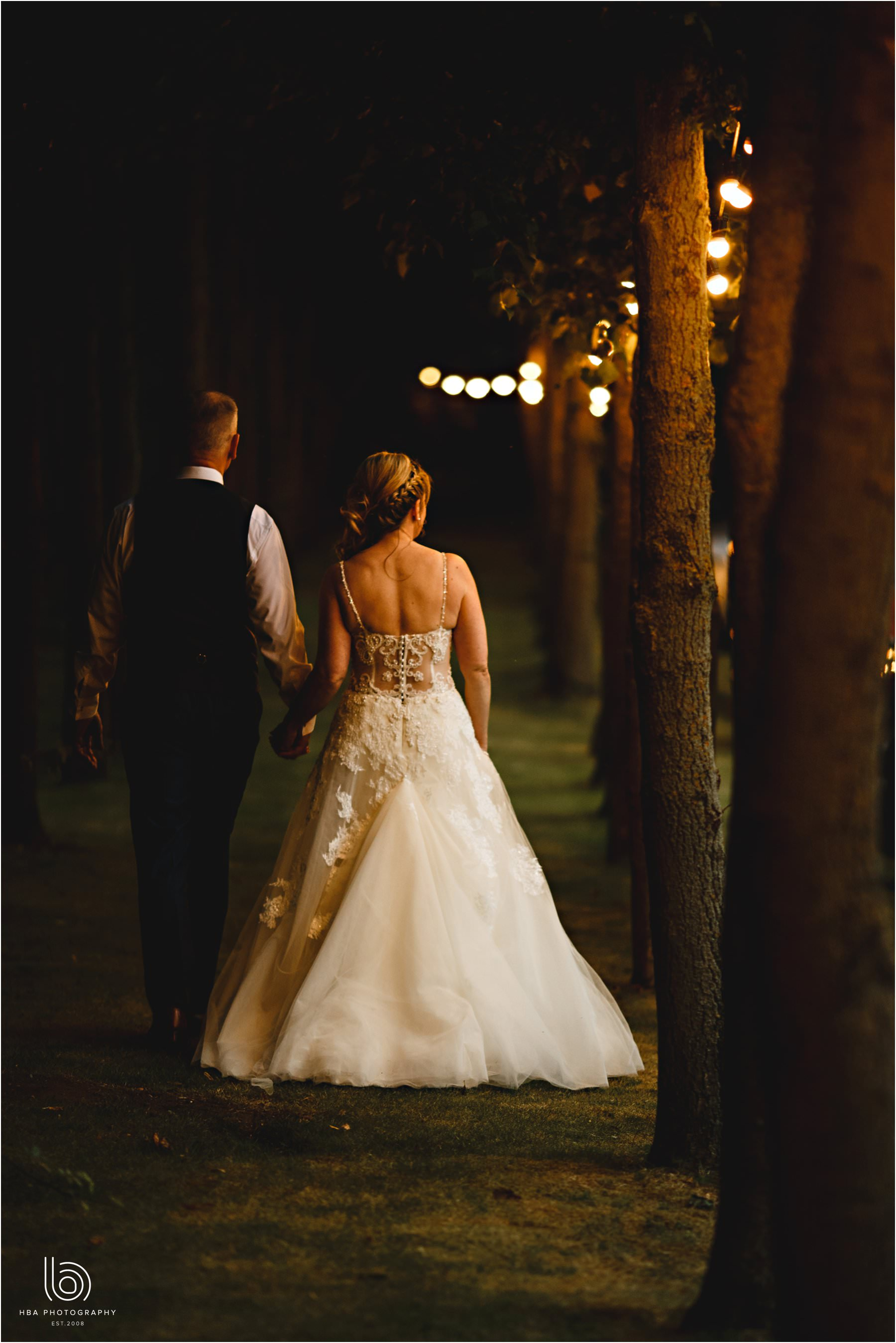 the bride & groom walking through the festoon lights