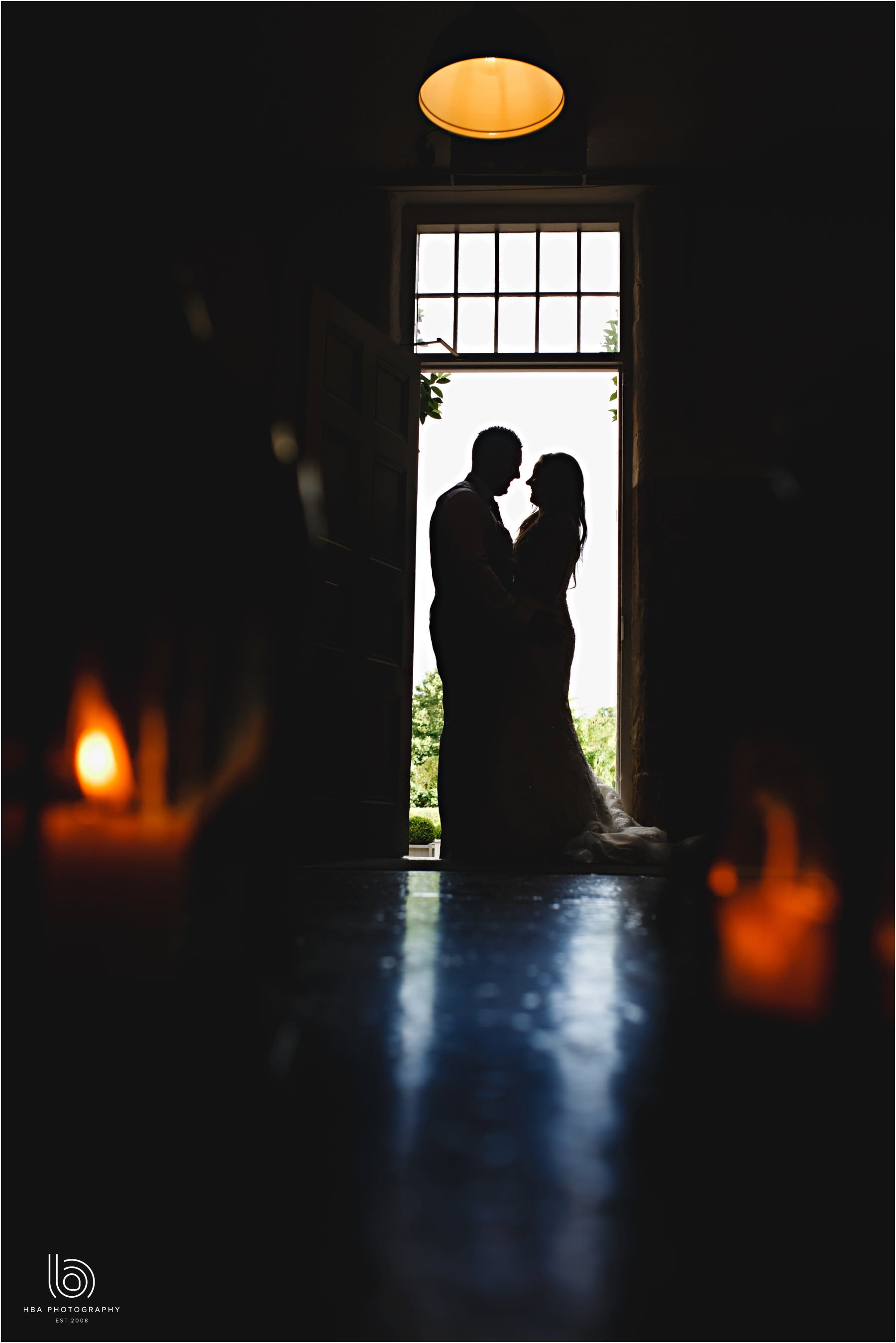 the bride & groom in silhouette by the front door