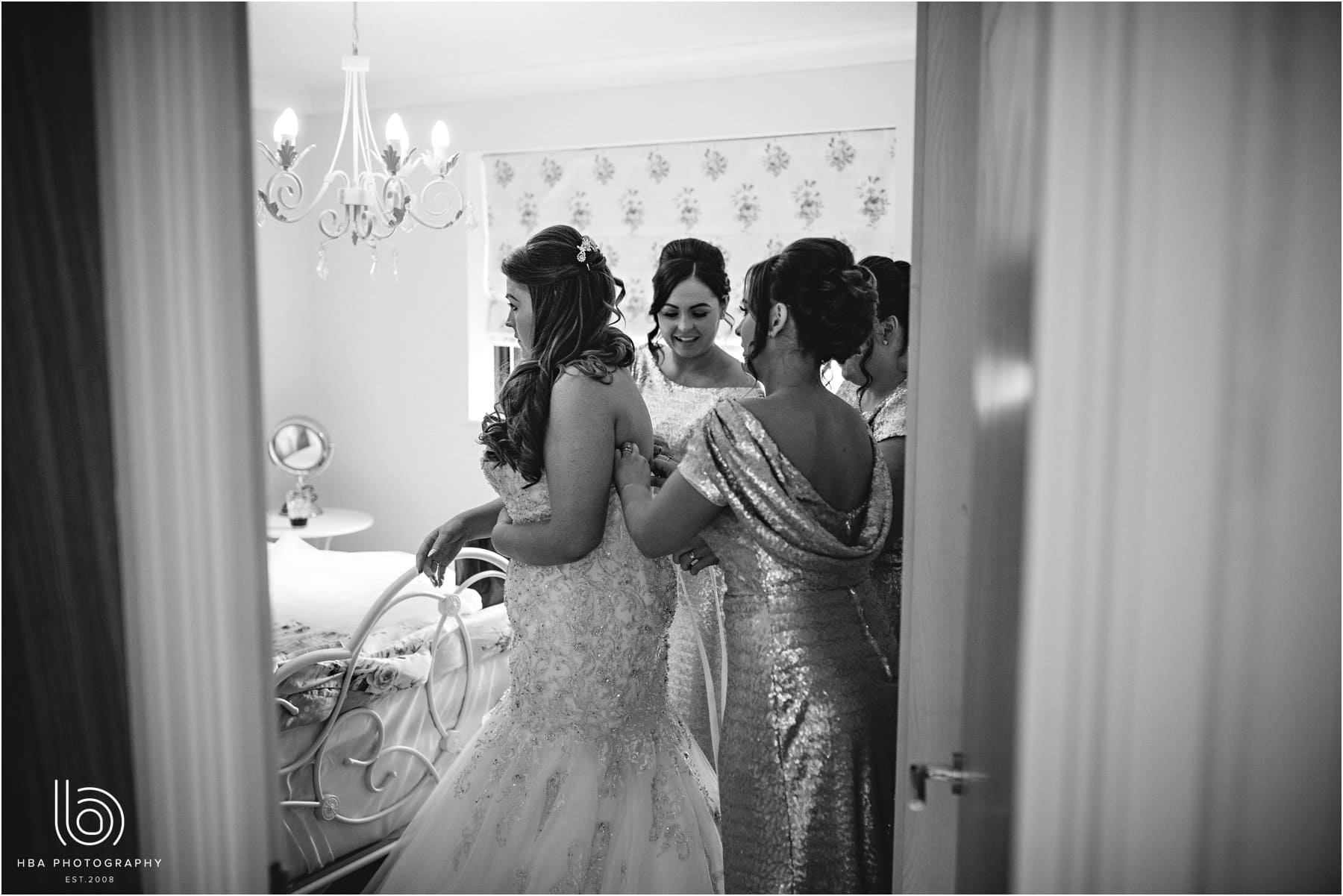 the bridesmaids helping the bride