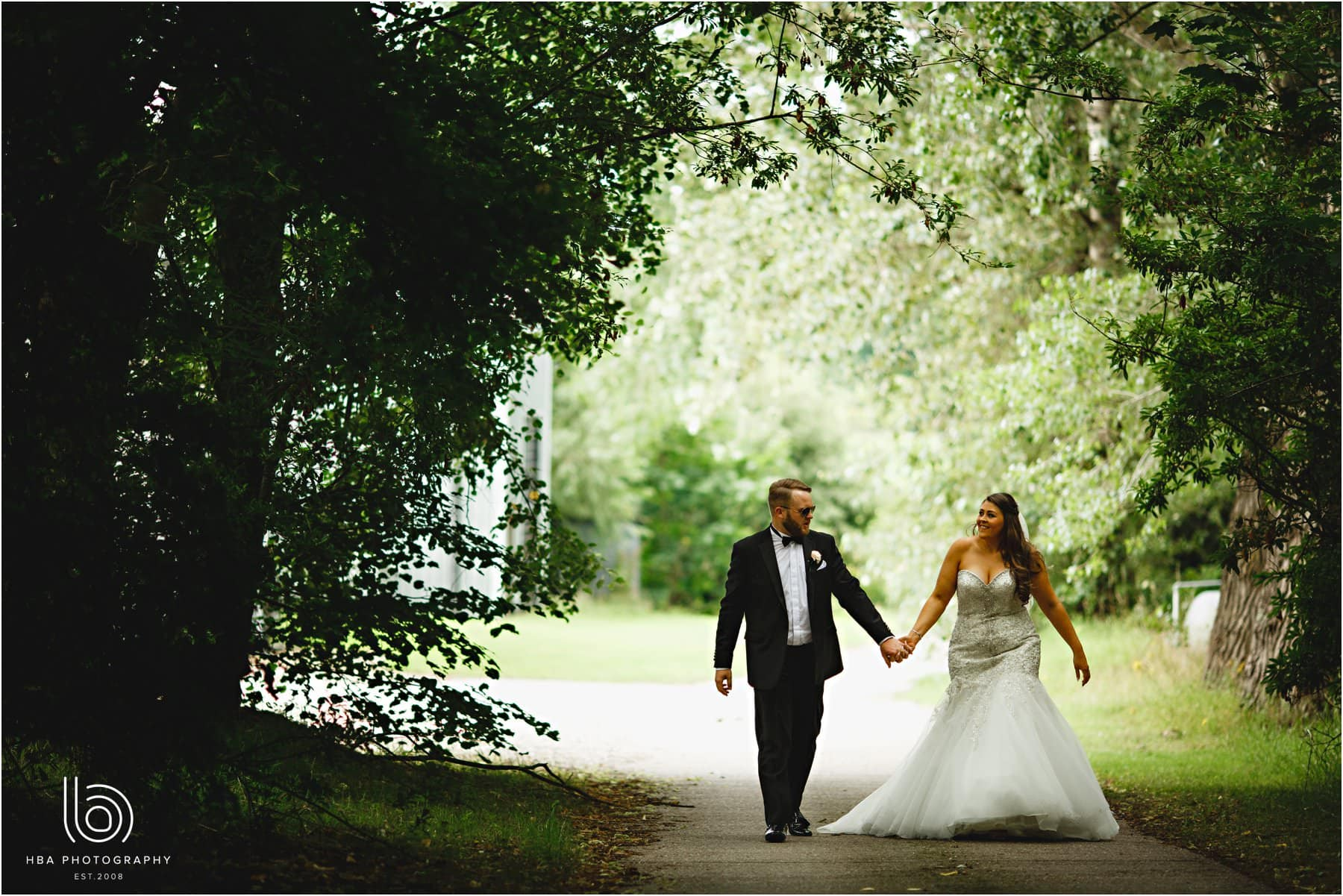 the bride & groom walking in the woods