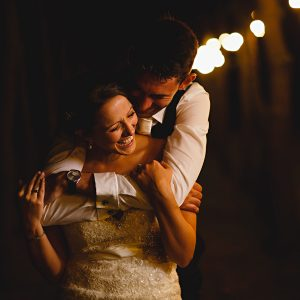Kirsty and Luke stood in the evening lights at Shustoke Farm Barns on their wedding day