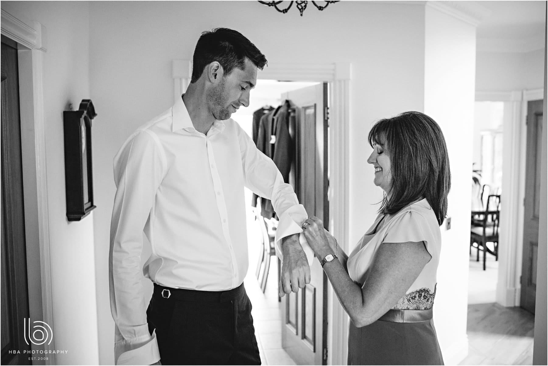 the groom's mum doing his cufflinks