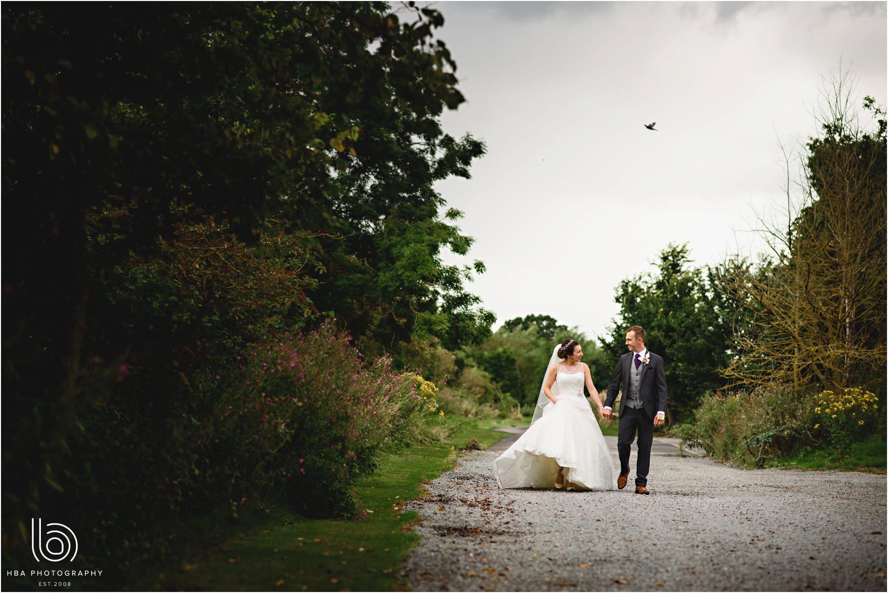 the bride & groom walking down the road at Shustoke]