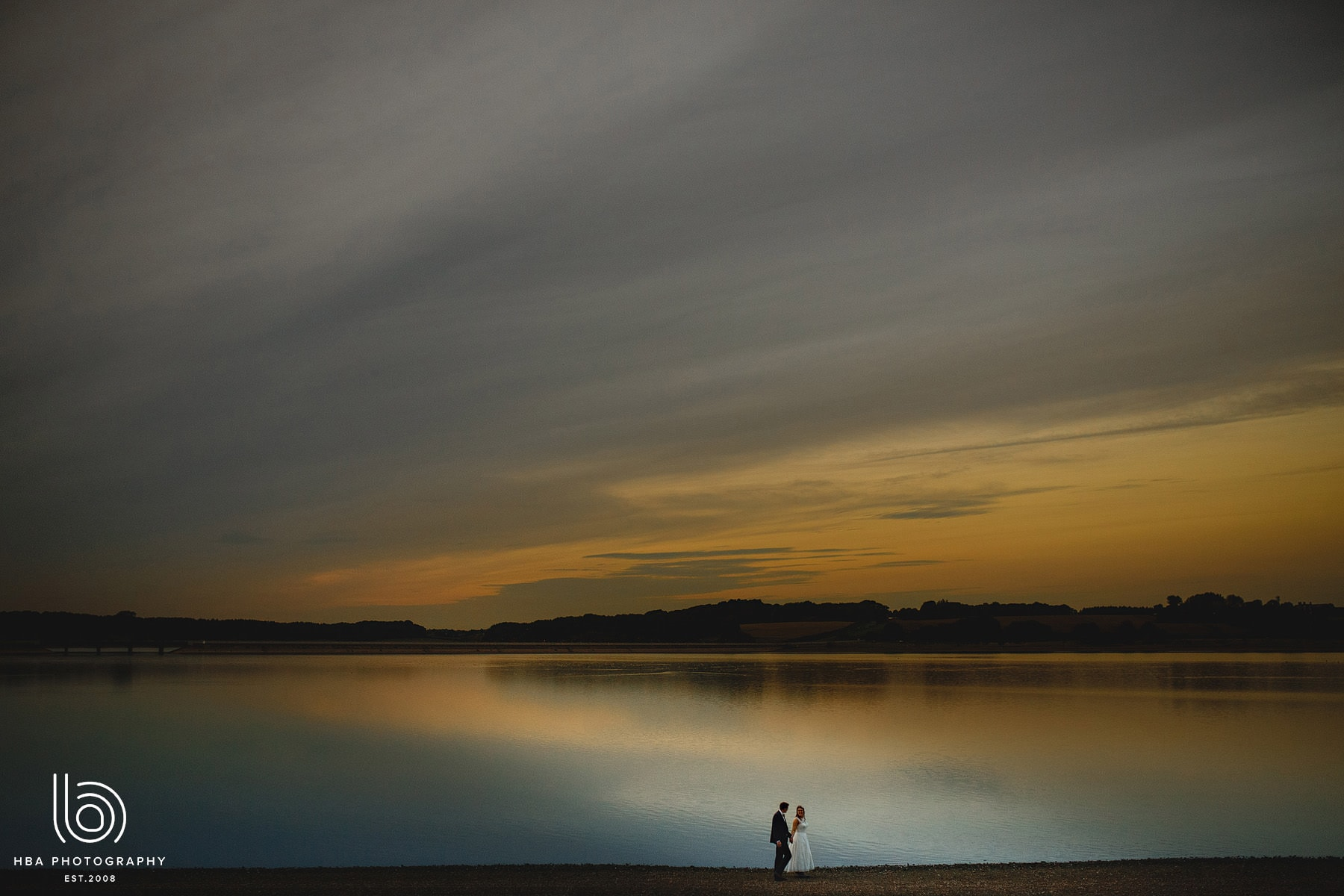 The bride & groom at sunset by the water