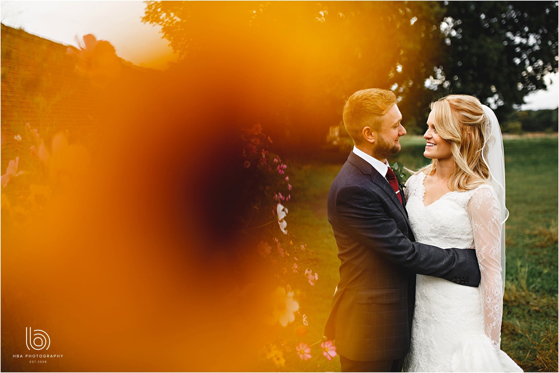 the bride and groom at Calke Abbey stood in orange flowers
