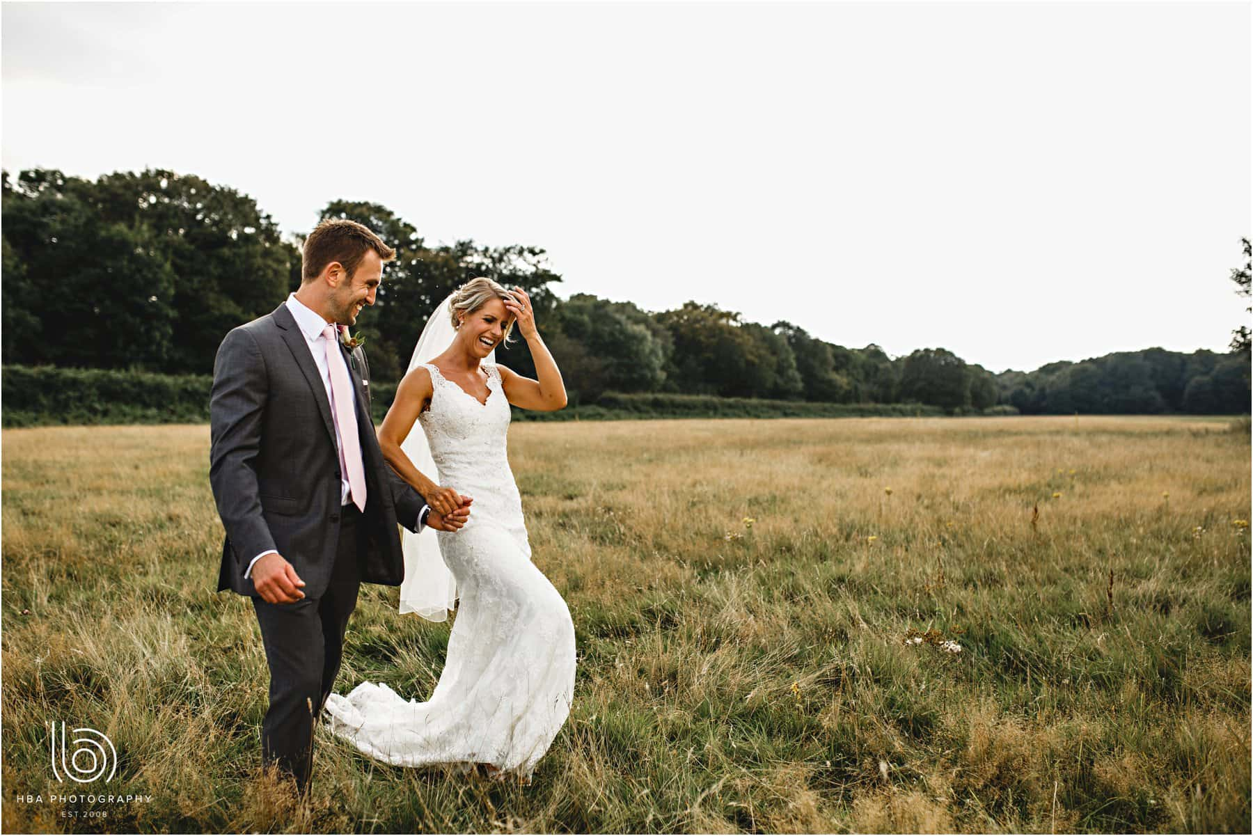 the bride and groom walking in the field