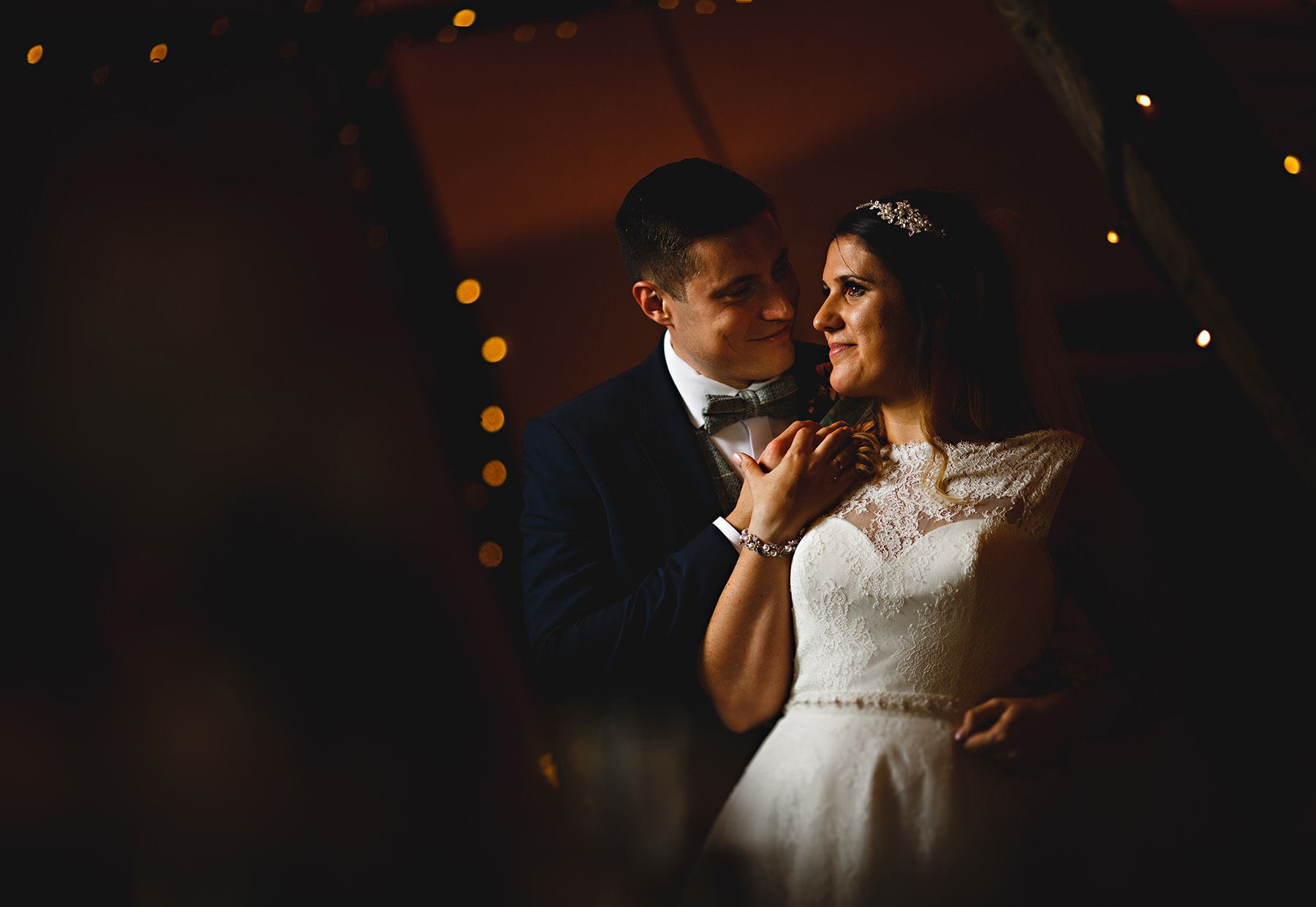 the bride and groom stood together inside the tipi on their wedding day