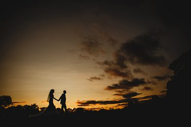 the bride and groom walking in orange sunset at Calke Abbey