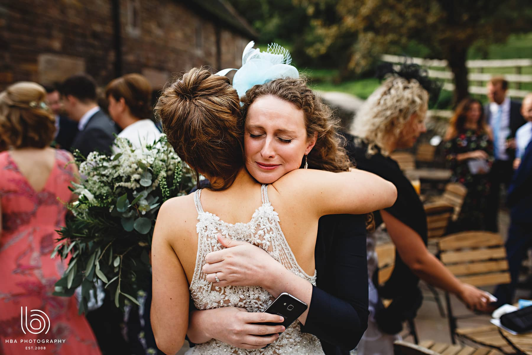 the bride being hugged by a guest