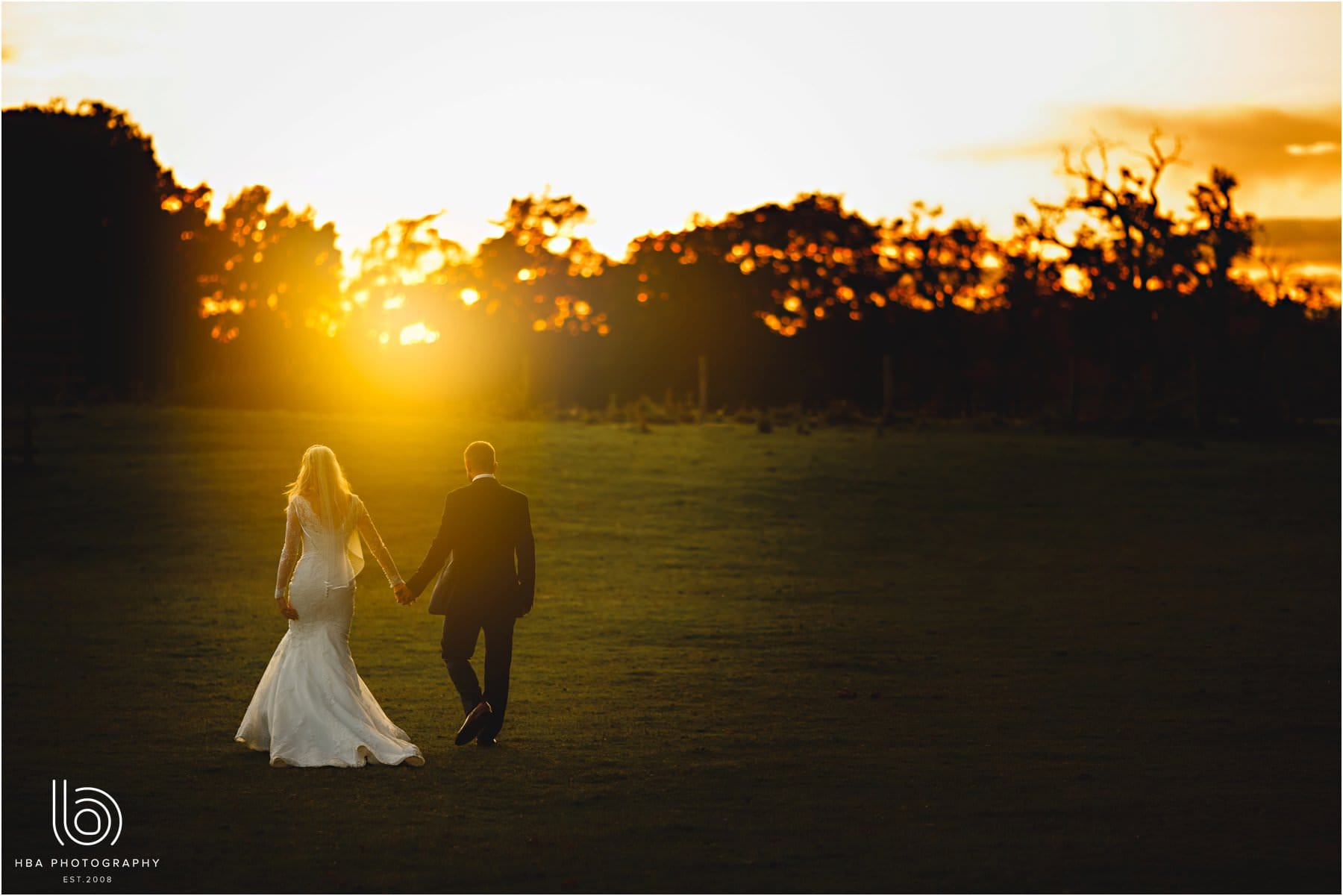 the bride & groom walking on the meadow at sunset