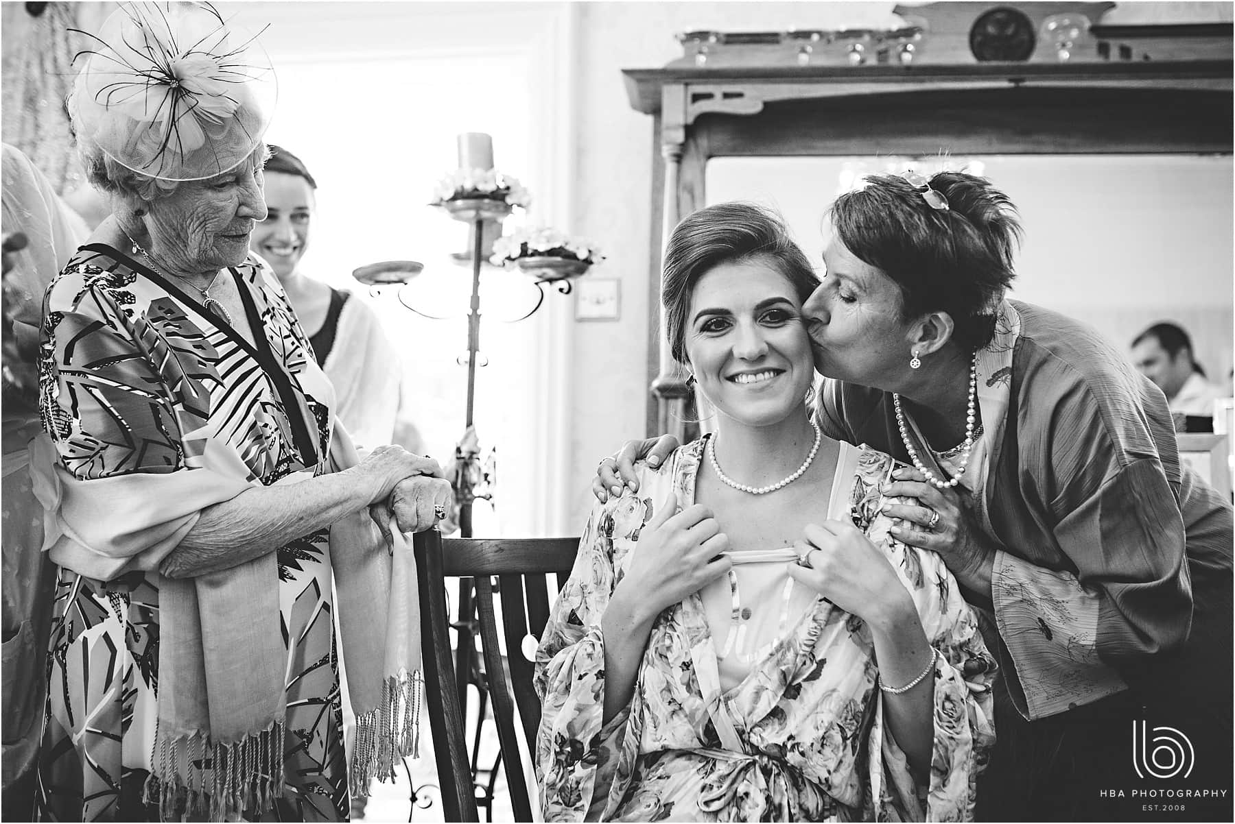 the bride's mum giving her a kiss