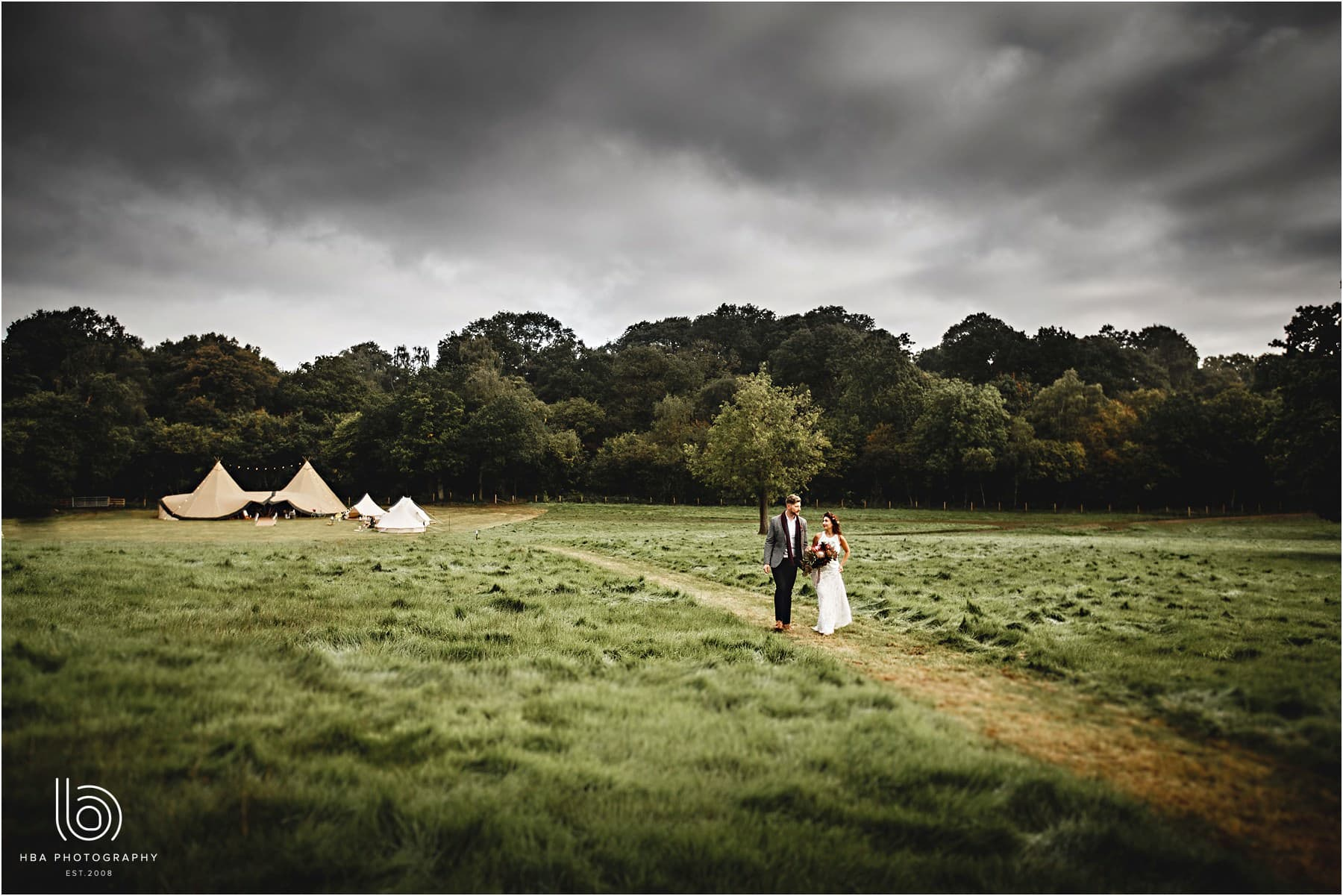 Bride and groom walking in the field with the tipi in the background