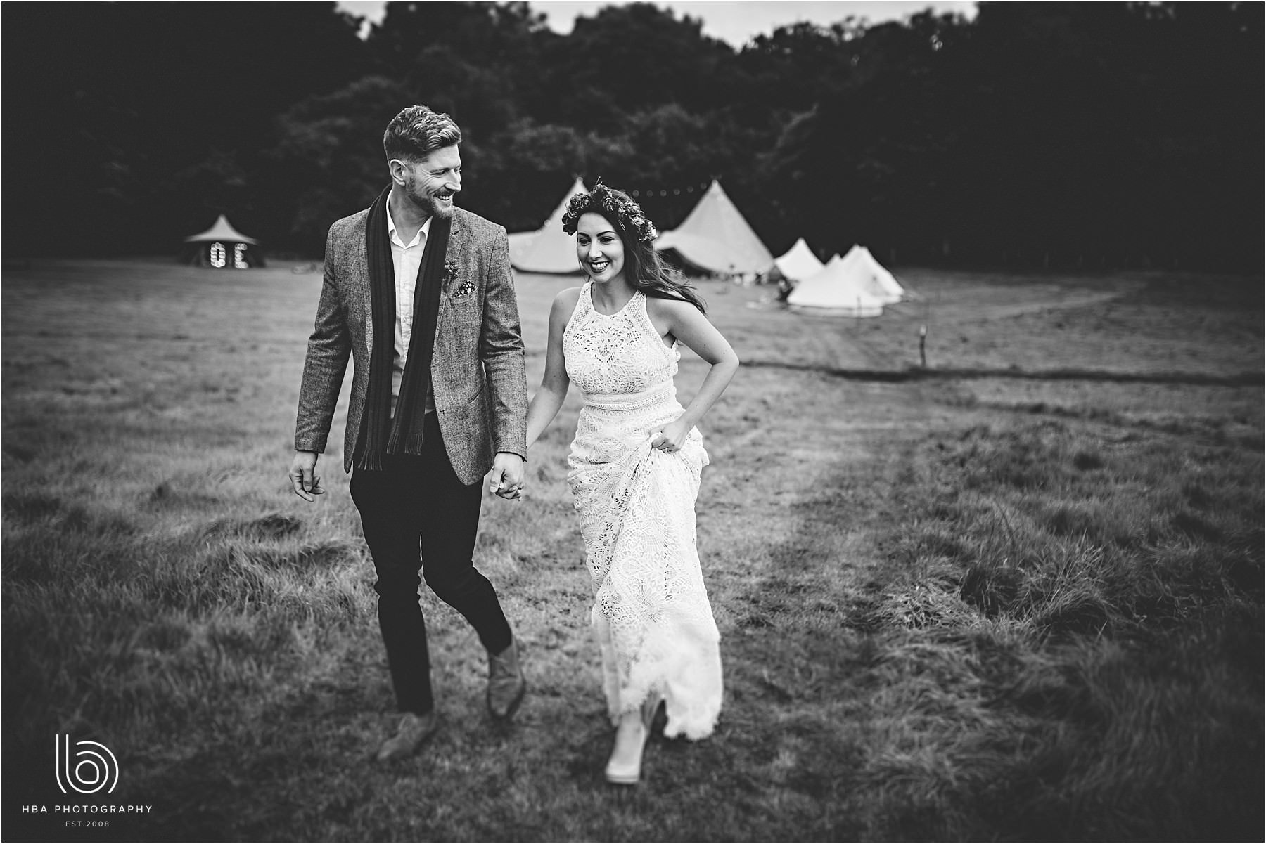 Bride and groom wlaking away from the tipis