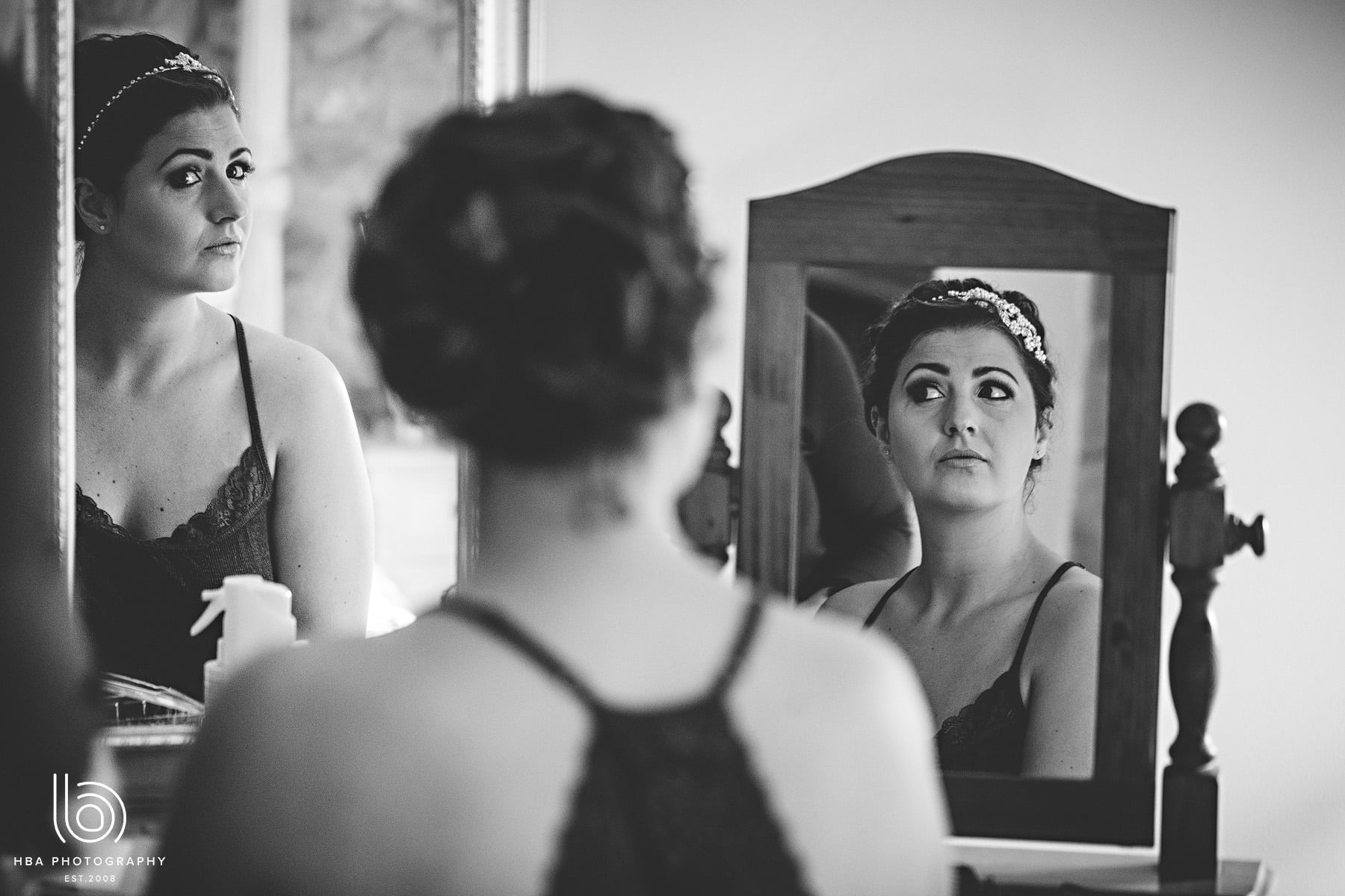 the bride looking at her hair in the mirror