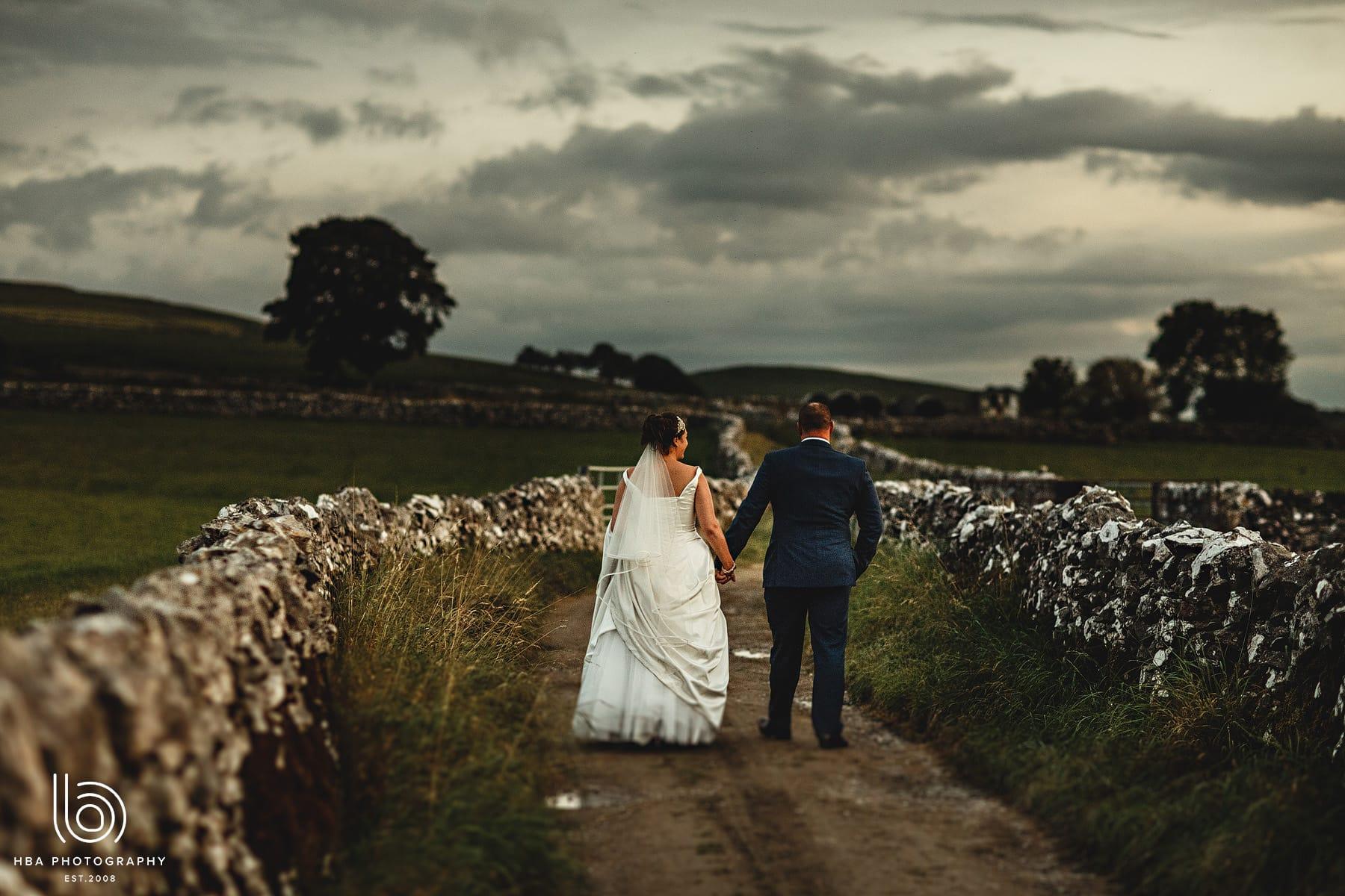 the bride & groom walking up a lane in Hartington