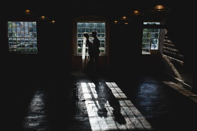 the bride and groom stook in beautiful window light at the West Mill