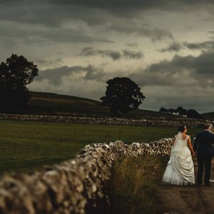 the bride and groom walking down a country lane at Hartington Hall