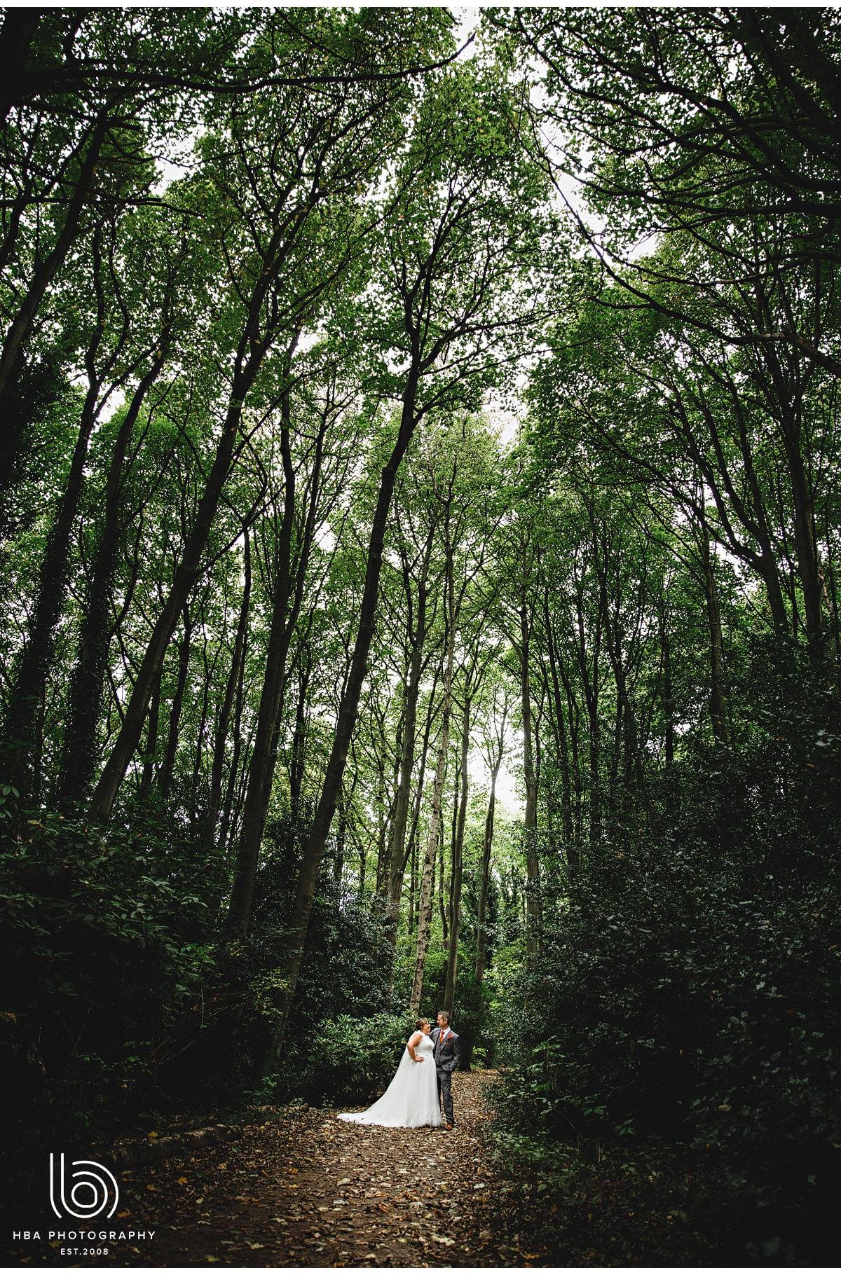 the bride & groom walking in the woods