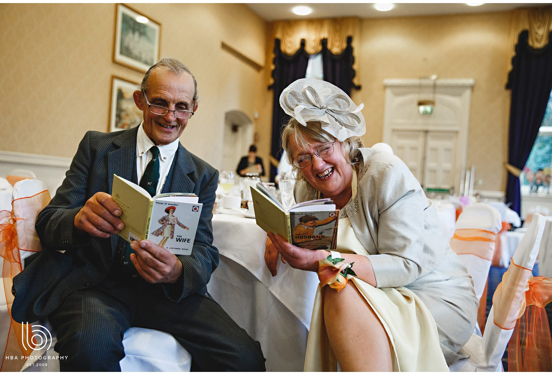 the mother of the bride and her brother laughing at a marriage book