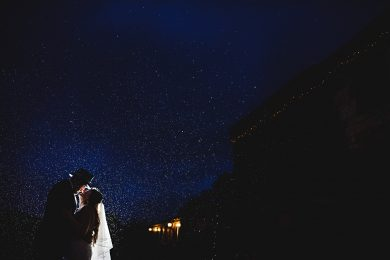The bride and groom dancing in the rain