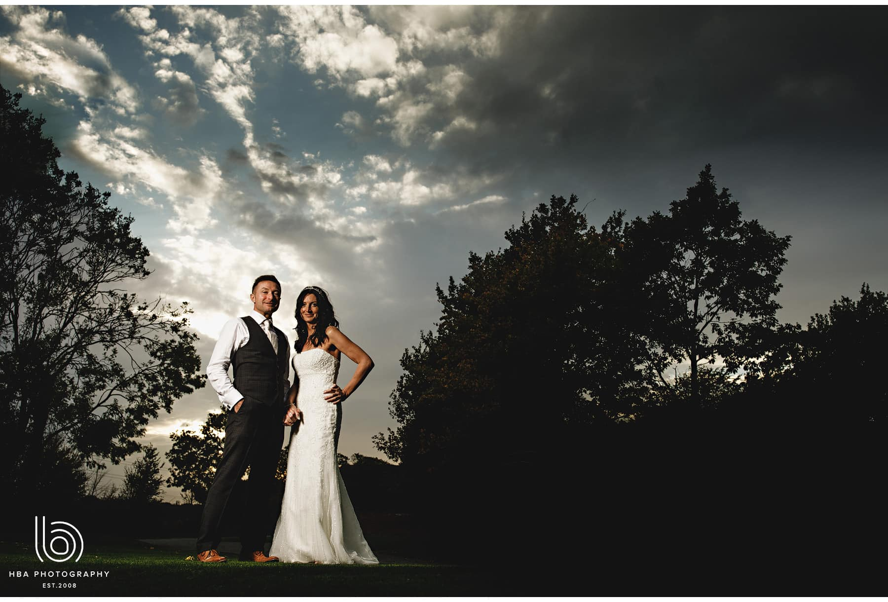 the bride & groom in a dramatic sky