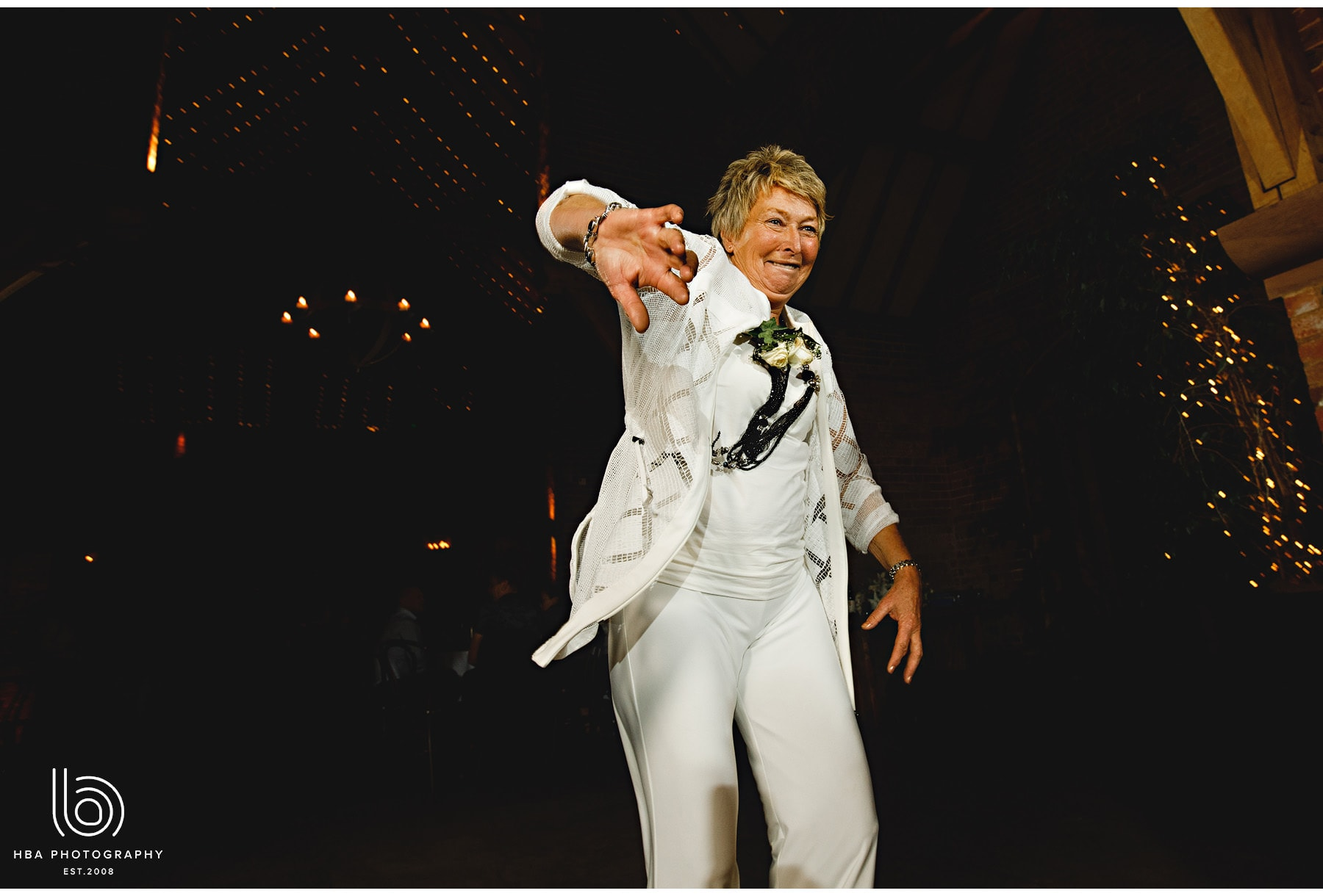 wedding guest in white suit dancing