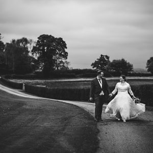a black and white photo of the bride and groom walking up the driveway