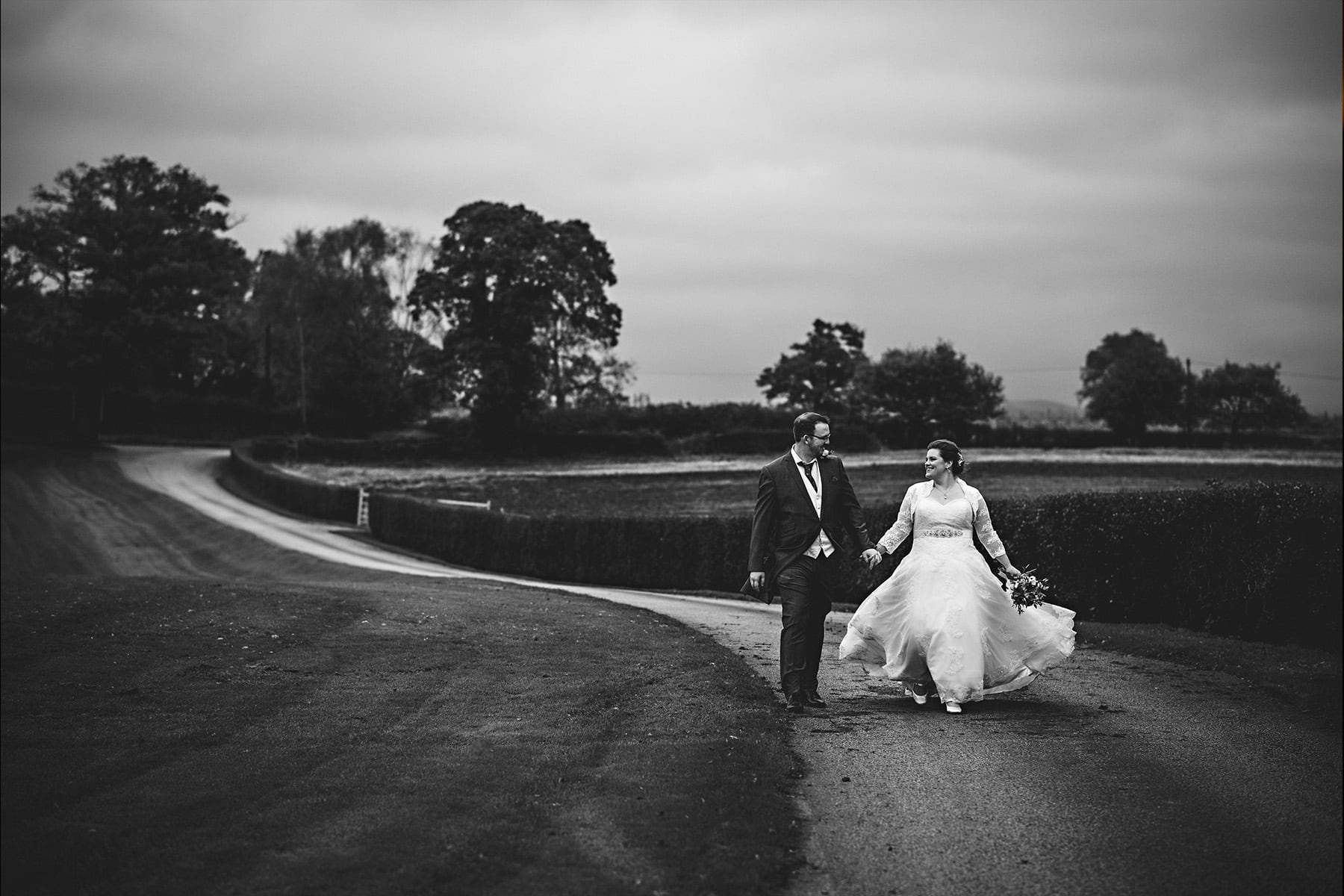 Sandhole Oak Barns. A black and white photo of the bride and groom walking up the driveway