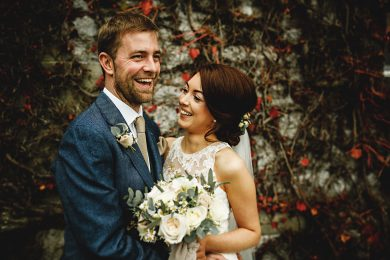 the bride and groom together in front of the red ivy at Callow Hall in Ashbourne