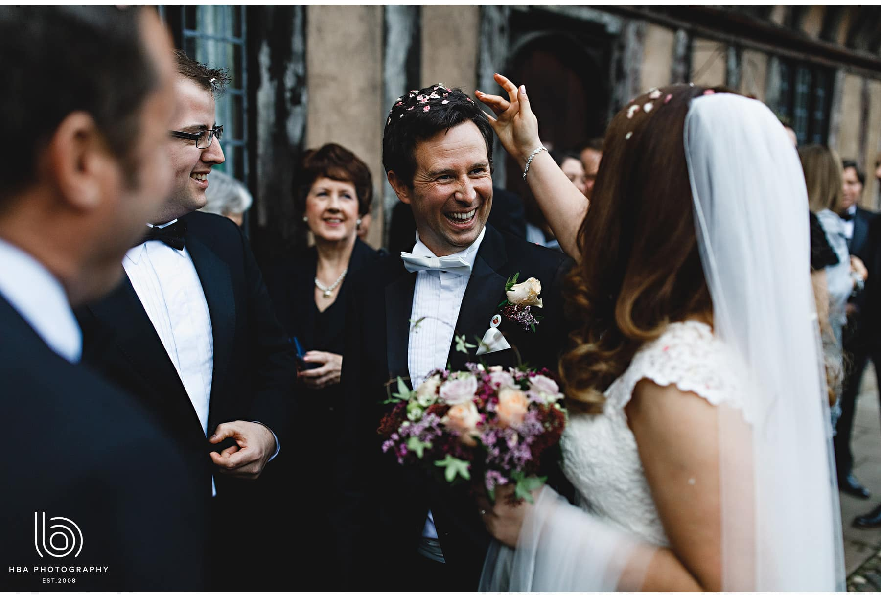 the groom with confetti in his hair