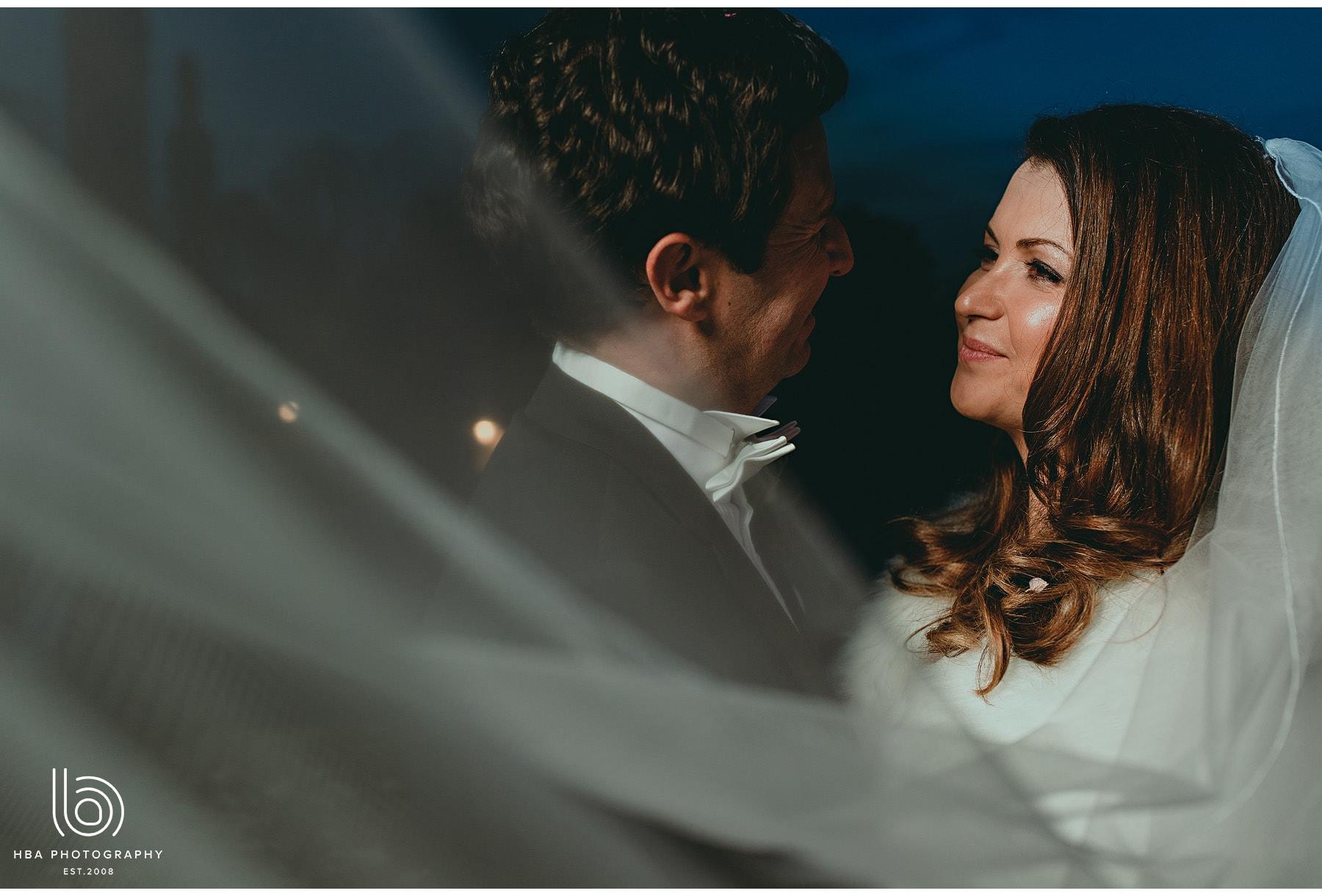 the bride & groom through the veil