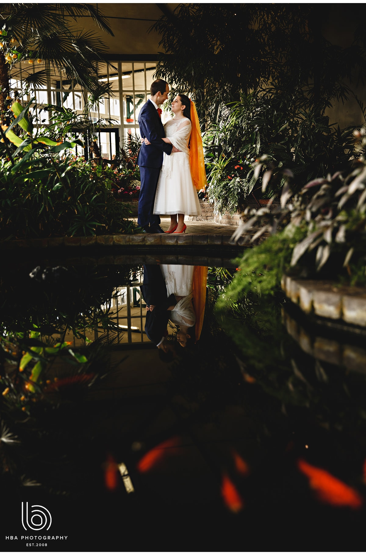 the bride and groom reflected in the pond