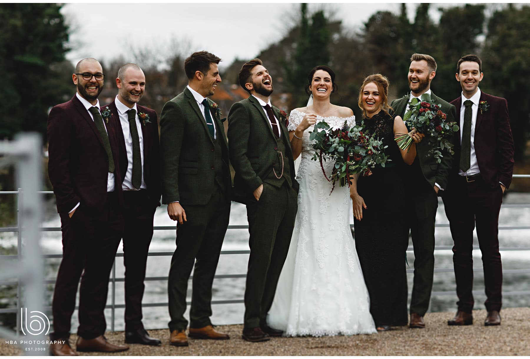 the bride & groom with the bridal party laughing